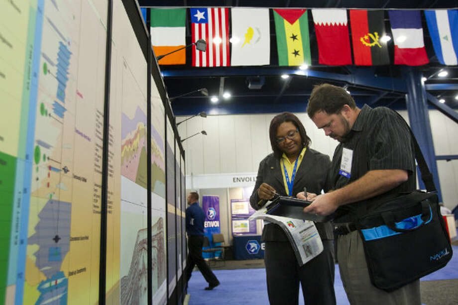 Sharon Kuhn, exploration geologist for Staatsolie, talks about oil lease blocks in Suriname with Sean Lewis, of ExxonMobile, during the NAPE Expo at the George R. Brown Convention Center Tuesday, Feb. 5, 2013, in Houston.