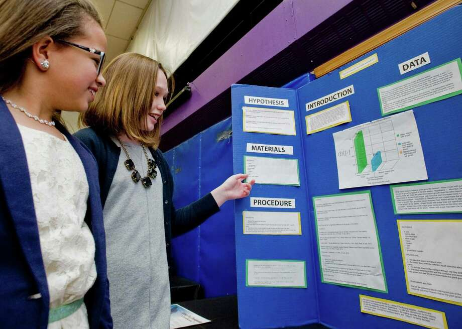 Isabella Echavarria and Finan Deakin, sixth-graders at St. Joseph School on Main Street in Danbury, explain their science project which investigated the type of liquids in which plants grow fastest, at the school's science fair, Wednesday, Feb. 6, 2013 Photo: Scott Mullin / The News-Times Freelance