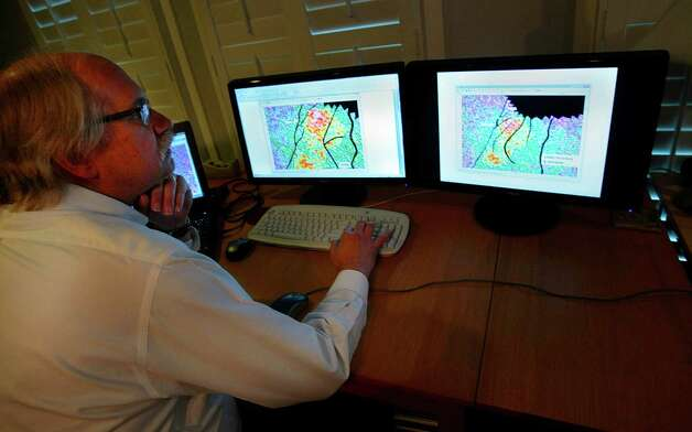 (l-r) Geophysicist Brain Kalinec of I.P. Petroleum looks at geophysical maps of the Spindeltop area Wednesday, February 6, 2013.  Kalinec along with his team are planning to drill for oil in Spindletop, and have put together a presentation for the NAPE conference. (Billy Smith II / Houston Chronicle) Photo: Billy Smith II, Staff