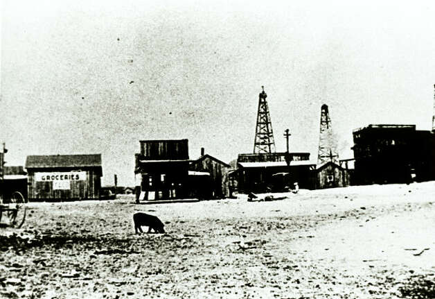 A pig roams past shops in Gladys City, the boomtown at Spindletop.