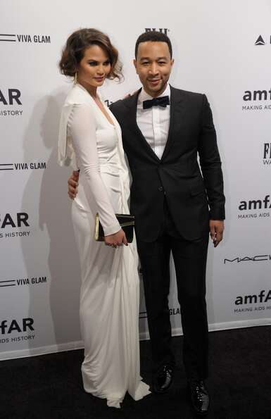 Singer John Legend (R) and Chrissy Teigen (L) arrive at the amfAR (The Foundation for AIDS Research)