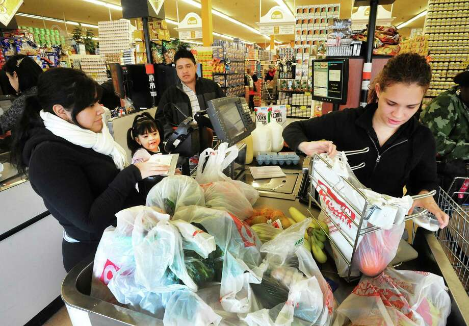 Silvana Gutierrez, her daughter, Sofia Salazar, 2, and Leonardo Salazar stock up on groceries in preparation for the comming storm at C-Town in Danbury. Yari Zapata, who is bagging their purchases, said the market was especially busy Thursday, Feb. 7, 2013.. Photo: Michael Duffy / The News-Times