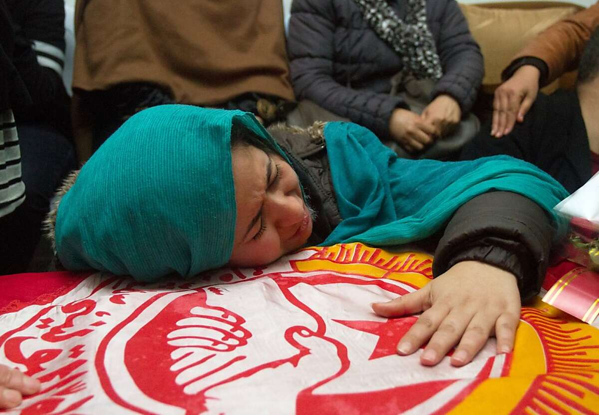 A relative of slain opposition leader Chokri Belaid cries at his coffin at the parents' home near Tunis, Thursday, Feb.7, 2013. The Islamist party dominating Tunisia's ruling coalition on Thursday rejected its own prime minister's decision to form a non-partisan technocratic government to try to appease critics, signaling that the political crisis brought on by the assassination of a prominent leftist politician is far from over. (AP Photo/Amine Landoulsi)