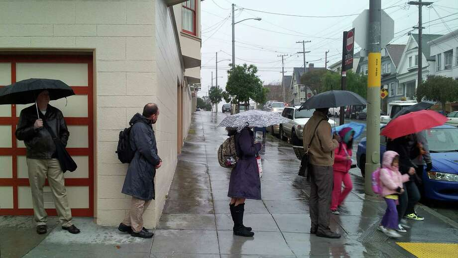 A line of bus riders wait for a bus during a  steady rainfall in the Richmond District of San Francisco Thursday morning. Photo: SF Gate / Douglas Zimmerman