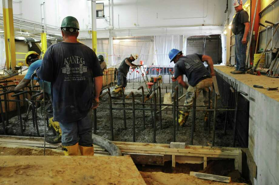 Workers pour in the first layer of concrete as work continues on the new press at the Times Union on Thursday, July 26, 2012 in Colonie, NY.   (Paul Buckowski / Times Union) Photo: Paul Buckowski / 00018491B