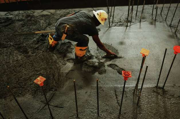 A workers smoothes over the surface of newly poured concrete as the first layer of concrete is poured as work continues on the new press at the Times Union on Thursday, July 26, 2012 in Colonie, NY.   (Paul Buckowski / Times Union) Photo: Paul Buckowski / 00018491B
