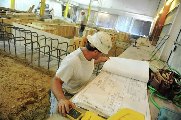 Concrete floorman Bill Bergdol looks at architectural designs as pit forms are intsalled for the floor in the new pressroom  on Tuesday, July 31, 2012 in Colonie, N.Y. (Lori Van Buren / Times Union) Photo: Lori Van Buren / 00018666A