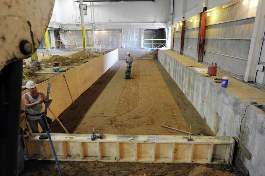 Workers prepare the area where five feet of concrete will be poured as work continues on the new pre