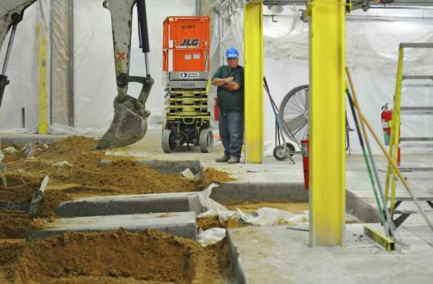 Workers remove the concrete floor of the old paper storage room as part of preparations for the new press at the Times Union,  on Wednesday June 27, 2012 in Colonie, NY. (Philip Kamrass / Times Union) Photo: Philip Kamrass / 00018281A