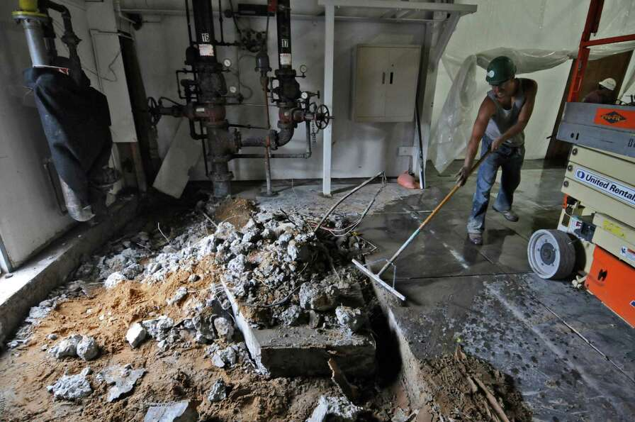 Workers cut the concrete floor of the old paper storage room as part of preparations for the new pre
