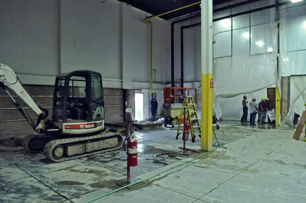 Workers cut the concrete floor of the old paper storage room as part of preparations for the new press at the Times Union,  on Monday June 25, 2012 in Albany, NY. (Philip Kamrass / Times Union) Photo: Philip Kamrass / 00018229A