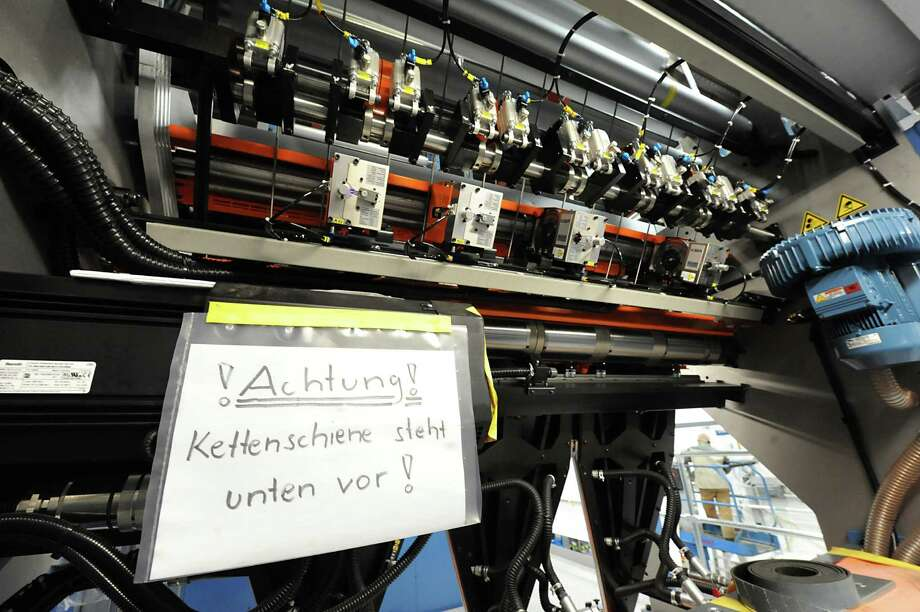 "A sign in German translates to ""Attention! chain rail is facing down"" on the new printing press at the Times Union on Tuesday Jan. 29, 2013 in Colonie, N.Y.  (Lori Van Buren / Times Union) Photo: Lori Van Buren"