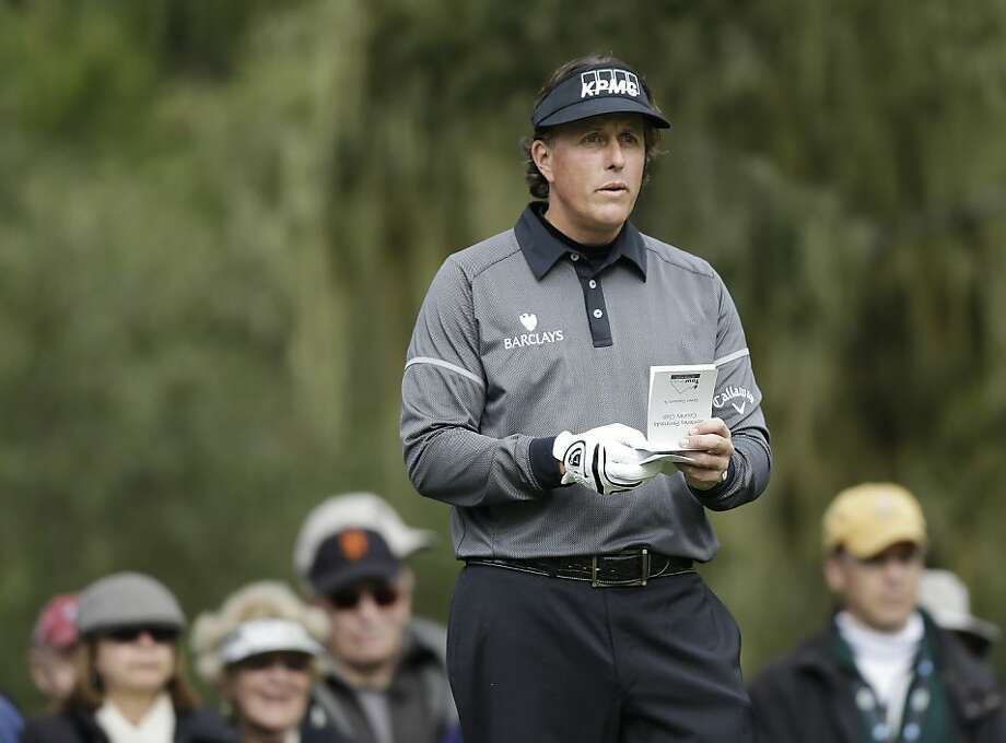 Defending champion Phil Mickelson checks his yardage book as he waits to hit from the third tee of the Monterey Peninsula Country Club Shore Course during the first round of the AT&T Pebble Beach Pro-Am golf tournament, Thursday, Feb. 7, 2013, in Pebble Beach, Calif. (AP Photo/Ben Margot) Photo: Ben Margot, Associated Press