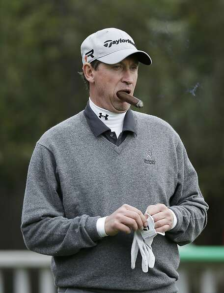 Hockey great Wayne Gretzky puffs on a cigar on the second green of the Monterey Peninsula Country Cl