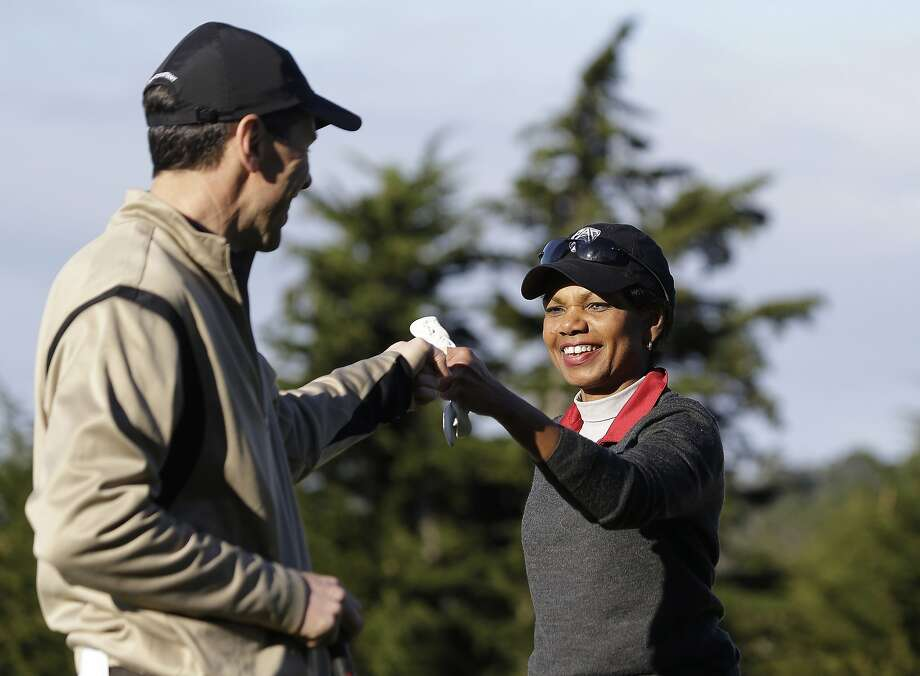 Former Secretary of State Condoleezza Rice, right, is greeted by Randall Stephenson, left, after making a putt to save par on the second green of the Pebble Beach Golf Links during the first round of the AT&T Pebble Beach Pro-Am golf tournament Thursday, Feb. 7, 2013, in Pebble Beach, Calif. (AP Photo/Eric Risberg) Photo: Eric Risberg, Associated Press