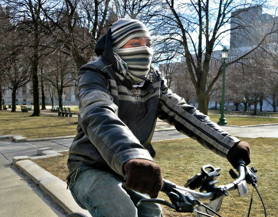 Shawn Haymon of Albany is bundled up for a cold bicycle ride past the Capitol in Albany Thursday Feb. 7, 2013.  (John Carl D'Annibale / Times Union) Photo: John Carl D'Annibale / 10021077A
