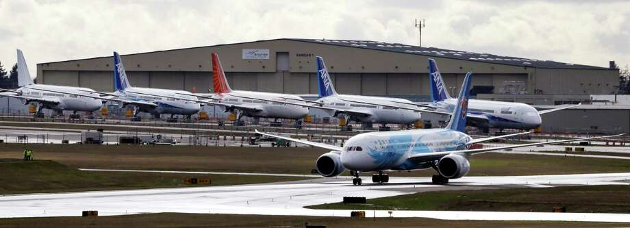 A Boeing 787 jet taxies past a line of parked 787's after landing Thursday, Feb. 7, 2013, at Paine Field in Everett, Wash., following a flight from Texas. The Federal Aviation Administration gave Boeing permission to relocate the plane, which was at Meacham Airport for painting when the planes were grounded last month by battery problems. Photo: AP