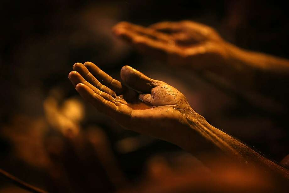 Hands of the devotees: An initiate of the Hindu Juna Akhara sect vows to sever his worldly ties and dedicate himself to God as a Naga, or naked holy man, during a ritual at Sangam, the confluence of the Ganges and Yamuna rivers in Allahabad, India. Photo: Manish Swarup, Associated Press