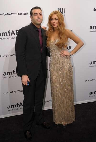 Mohammed Al Turki (L) and Lindsay Lohan (R) arrive at the amfAR (The Foundation for AIDS Research) g