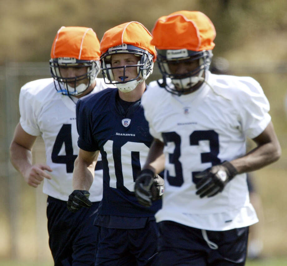 From left, Seattle Seahawks linebacker Dane Krager, wide receiver Jerheme Urban and cornerback Doug Evans wear orange helmet covers while taking part in a kickoff drill during afternoon special teams practice Sunday, Aug. 17, 2003 at Seahawks training camp in Cheney, Wash. (AP Photo/Ted S. Warren) Photo: TED S. WARREN, Associated Press / AP