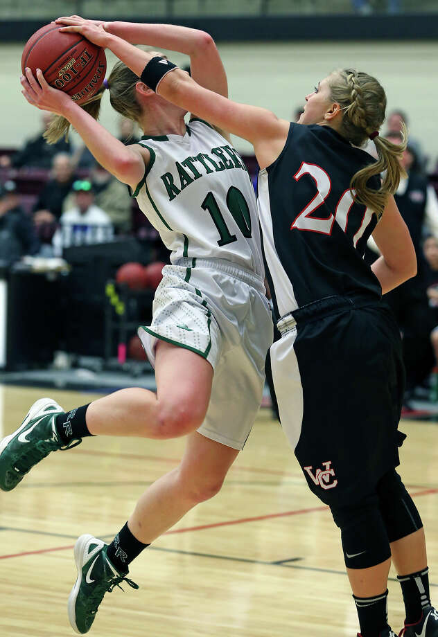 Wendy Knight tries a shot for the Rattlers but Leslie Vorpahl reaches to block as the Reagan girls play Churchill at Littleton Gym on January 15, 2013. Photo: Tom Reel, Express-News / ©2012 San Antono Express-News