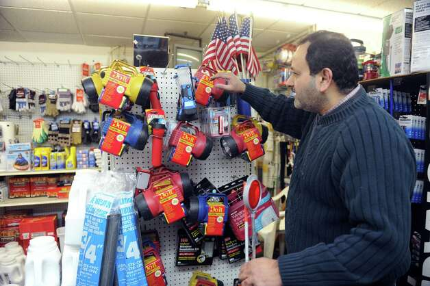 Frank Kudia, a new owner of Cos Cob Hardware, shows the flashlights for potential snow storm Thursday, Feb. 7, 2013. Photo: Helen Neafsey / Greenwich Time