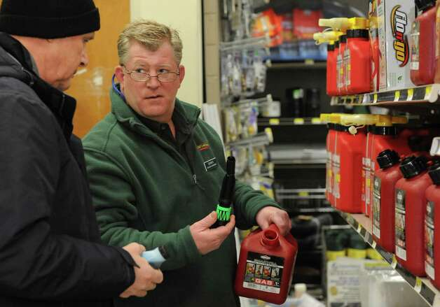 Dennis Ross shows Drew Bisset, left, how to mix gasoline for his leaf blower, which he plans to use to clear snow, at Keough's Paint and Hardware in Stamford on Thursday, February 7, 2013, in preparation for winter storm Nemo. Photo: Lindsay Perry / Stamford Advocate