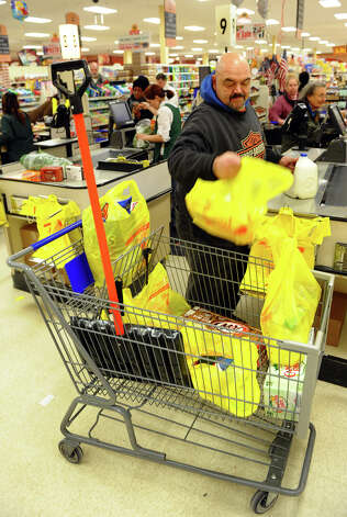 Phil Cervero, of Stratford, puts groceries in his cart after doing some shopping at ShopRite in Stratford, Conn. on Thursday February 7, 2013. Cervero also bought a shovel to replace the one his son took, so he could be ready for the big snow storm expected to hit the region Friday and Saturday. Photo: Christian Abraham / Connecticut Post