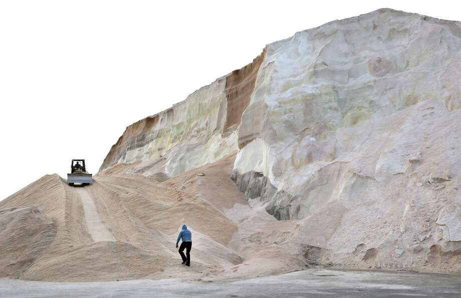 A worker walks up towards a plow smoothing a large salt pile at Eastern Salt Company in Chelsea, Mass., Thursday, Feb. 7, 2013, in preparation for a major winter storm headed toward the U.S. Northeast. The National Weather Service calls for up to 2 feet of snow expected for a Boston-area region that has seen mostly bare ground this winter. (AP Photo/Elise Amendola) Photo: Elise Amendola, Associated Press / AP