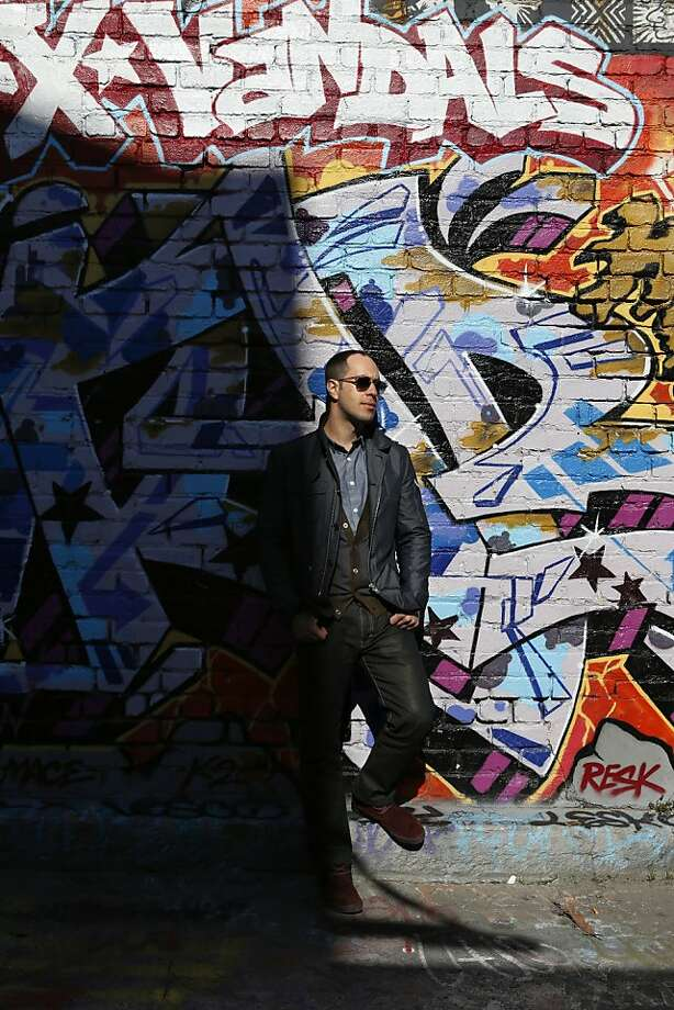 "Berkeley writer Adam Mansbach, a self-described ""aficionado of graffiti,"" surveys graffiti in a San Francisco alley. Photo: Beck Diefenbach, Special To The Chronicle"