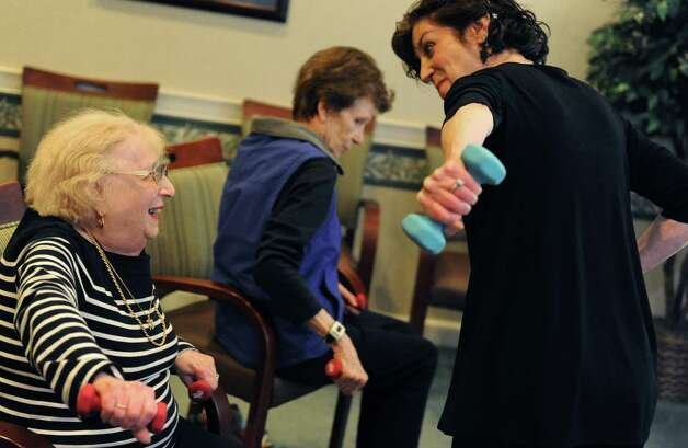 Irma Herz, left, participates in an exercise class with instructor Sandi Sacks at Atria in Stamford on Thursday, December 7, 2013. Photo: Lindsay Perry / Stamford Advocate