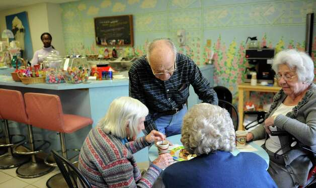 A group gathers in the ice cream shoppe at Atria in Stamford on Thursday, December 7, 2013. At the table are, clockwise from left, Peggy Glynn, volunteer Max Silver, Eve Hine and Liz Gellmann. Photo: Lindsay Perry / Stamford Advocate