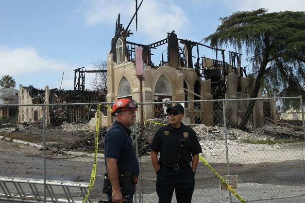 Mike Littrell (left), Senior Fire Investigator with Premier Claims Investigations, speaks Thursday February 7, 2013 with San Antonio Fire Captain Fernando Sosa (right) in front of the remains of Childress Memorial Church of God in Christ at 901 North Pine. The church burned down last Friday and agents from the Bureau of Alcohol, Tobacco, Firearms and Explosives have been investigating the cause of the fire. It appeared that most of the agents at the scene had left by Thursday. Photo: JOHN DAVENPORT, San Antonio Express-News / ©San Antonio Express-News/Photo Can Be Sold to the Public