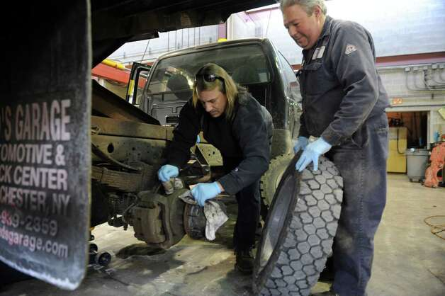 Paul Nastahowski, left, and Gene Pennella change a tire at the town John J. Kennedy Fleet Maintenance and Highway facility Thursday, Feb.7, 2013, to get ready for the next day's snowstorm. Photo: Helen Neafsey / Greenwich Time