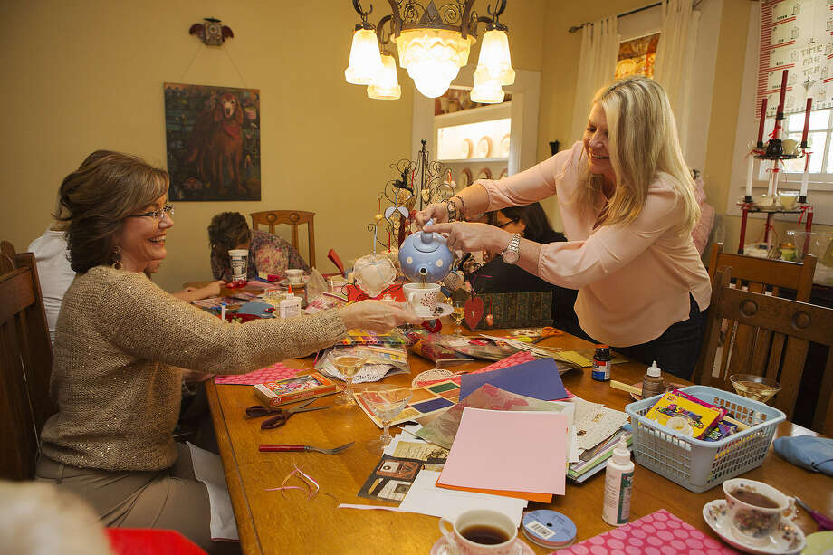 Becky Witte serves tea to guest Catherine Larsen at her recent Laundry Day tea party. Witte and her friends create Valentine's Day cards and nibble homemade goodies at the get-togethers. Photo: Photos By Michael Miller / For The Express-News