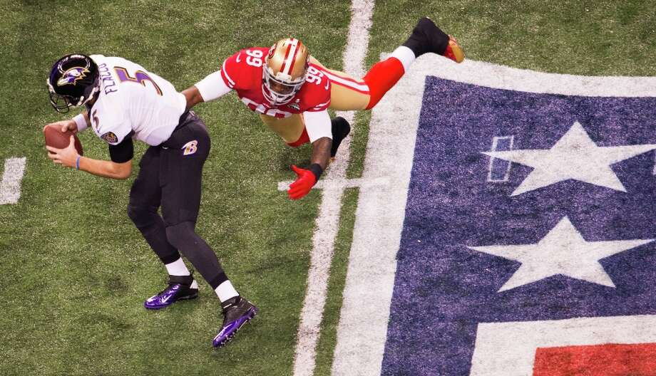 Baltimore Ravens quarterback Joe Flacco (5) slips away from San Francisco 49ers outside linebacker Aldon Smith (99) during the second half of Super Bowl XLVII at the Mercedes-Benz Superdome on Sunday, Feb. 3, 2013, in New Orleans. Photo: Smiley N. Pool, Chronicle / ONLINE_YES