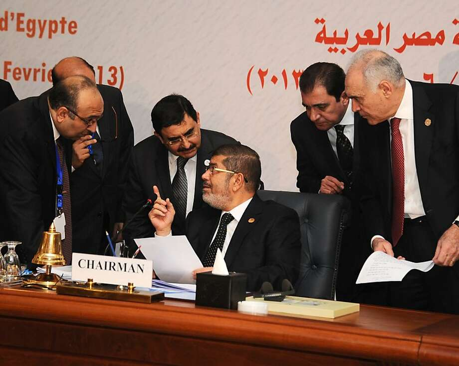 Egyptian President Mohammed Morsi (center) confers with other leaders attending the Organization of Islamic Cooperation Summit in Cairo. Photo: Anonymous, Associated Press