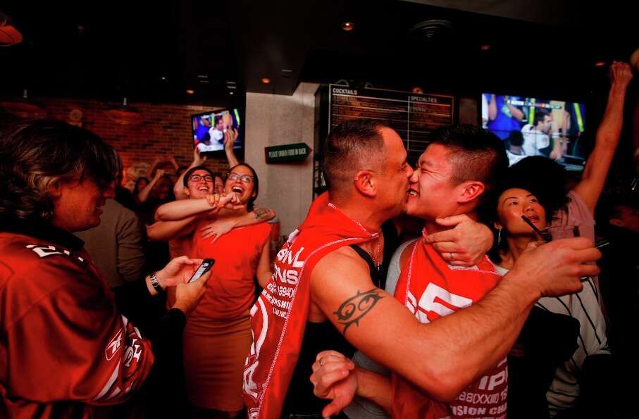 Markus Merlino, left,  kisses his husband Alan as they celebrate the San Francisco 49er scoring in t