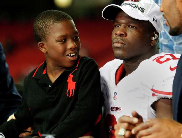 Little Frank looked at his father Frank Gore while waiting for an interview. The San Francisco 49ers beat the Atlanta Falcons 28-24 to win the NFC title and advance to the Super Bowl Sunday January 20, 2013. Photo: Brant Ward, The Chronicle / ONLINE_YES