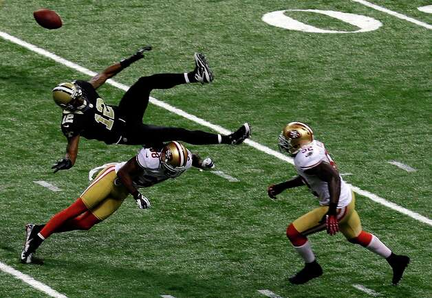 New Orleans Saints wide receiver Marques Colston (12) is upended by San Francisco 49ers safety Dashon Goldson (38), causing an interception returned for a touchdown, in the second half of an NFL football game in New Orleans, Sunday, Nov. 25, 2012. Photo: Bill Haber, Associated Press / FR170136 AP
