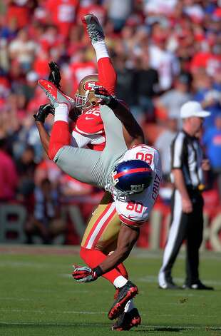New York Giants wide receiver Victor Cruz (80) is flipped over by San Francisco 49ers cornerback Carlos Rogers (22) during on an incomplete pass during the second half of an NFL football game in San Francisco, Sunday, Oct. 14, 2012. Photo: Mark J. Terrill, Associated Press / AP