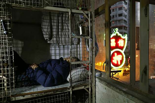 In this Jan. 25, 2013 photo, 62-year-old Cheng Man Wai lays in his cage, measuring 1.5 square meters (16 square feet),  which he calls home, in Hong Kong. For many of the richest people in Hong Kong, one of Asia's wealthiest cities, home is a mansion with an expansive view from the heights of Victoria Peak. For some of the poorest, home is a metal cage. Some 100,000 people in the former British colony live in what's known as inadequate housing, according to the Society for Community Organization, a social welfare group.  Photo: Vincent Yu, Associated Press