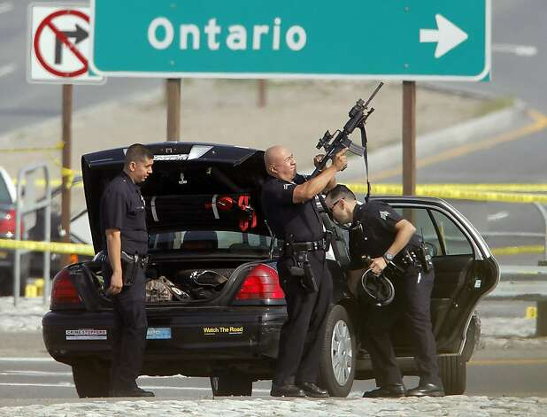 A Los Angeles Police officer checks his weapon at the site of a shooting Thursday Feb. 7, 2013 in Corona, Calif. Christopher Dorner is suspected of shooting two LAPD officers who were sent to Corona to protect someone Dorner threatened in a rambling online manifesto. Thousands of police officers throughout Southern California and Nevada hunted Thursday for Dorner, a former Los Angeles officer who was angry over his firing and began a deadly shooting rampage that he warned in an online posting would target those on the force who wronged him(AP Photo/Nick Ut) Photo: Nick Ut, Associated Press