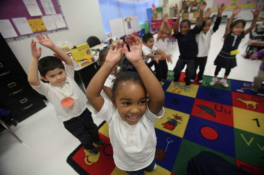 "Spanish speaking pre-kindergarten student Marcos Rangel, 5, and Kenadee Howard, 4, play ""arriba abajo game"" at Thurgood Marshall Early Childhood Center in Houston. Photo: Mayra Beltran, Houston Chronicle / Houston Chronicle"