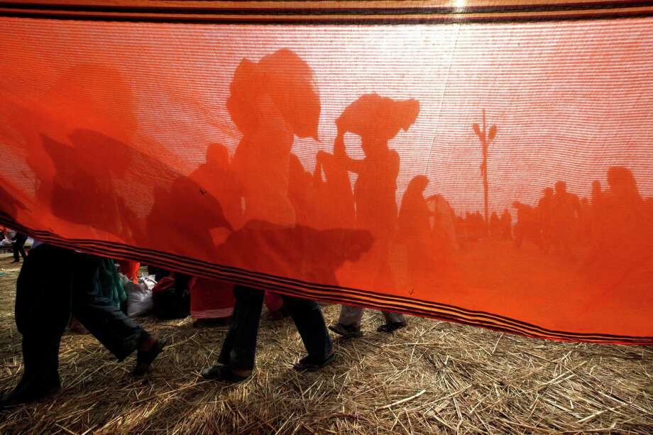 Indian devotees dry their cloths after a dip at Sangam, the confluence of the Ganges, Yamuna and mythical Saraswati River as others arrive during the Maha Kumbh festival in Allahabad, India Thursday, Feb. 7, 2013. Photo: Manish Swarup, Associated Press / AP