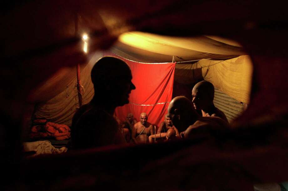 "Hindu holy men of the Juna Akhara sect take refuge in a tent following sudden rain during a ritual that is believed to rid them of all ties in this life and dedicate themselves to serving God as a ""Naga"" or naked holy men, at Sangam, the confluence of the Ganges and Yamuna River. Photo: Manish Swarup, Associated Press / AP"