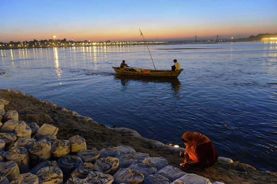 A woman prays by a candle light as two men use a boat to make their way upstream in the confluence of the Yomuna and the Ganges river at the Sangam during the Maha Kumbh festival in Allahabad on February 7, 2013. Photo: ROBERTO SCHMIDT, AFP/Getty Images / AFP