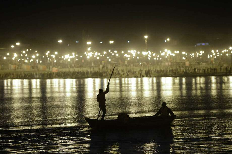 Two men use a boat to make their way upstream in the confluence of the Yomuna and the Ganges river at the Sangam during the Maha Kumbh festival in Allahabad. Photo: ROBERTO SCHMIDT, AFP/Getty Images / AFP