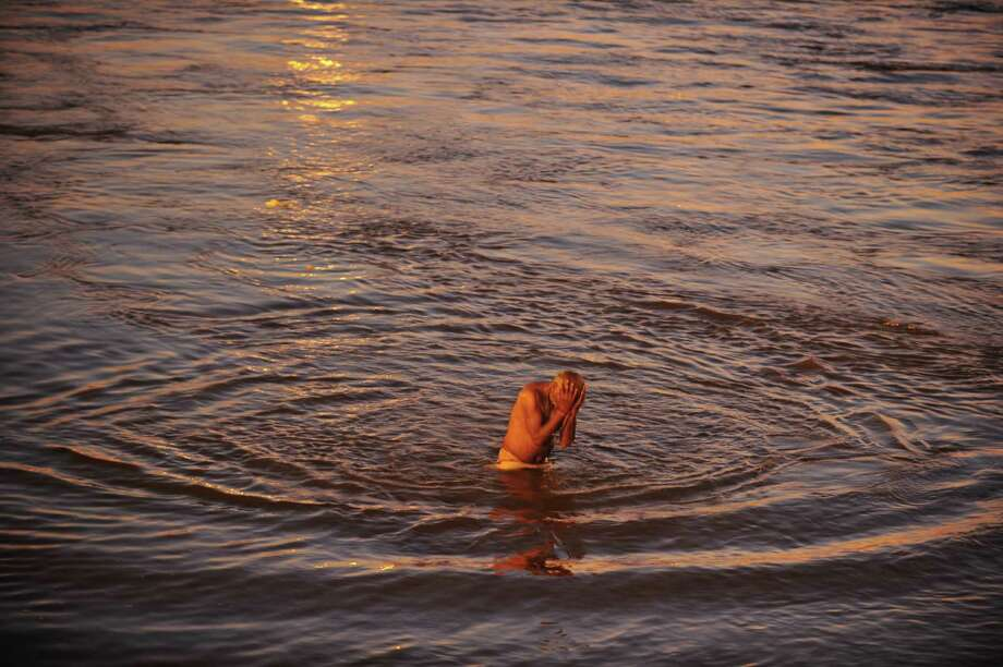 An Indian devotee takes a holy dip at the Sangam during the Maha Kumbh festival in Allahabad on February 7, 2013.  The Kumbh Mela in the town of Allahabad will see up to 100 million worshippers gather over 55 days to take a ritual bath in the holy waters, believed to cleanse sins and bestow blessings. Photo: SANJAY KANOJIA, AFP/Getty Images / AFP