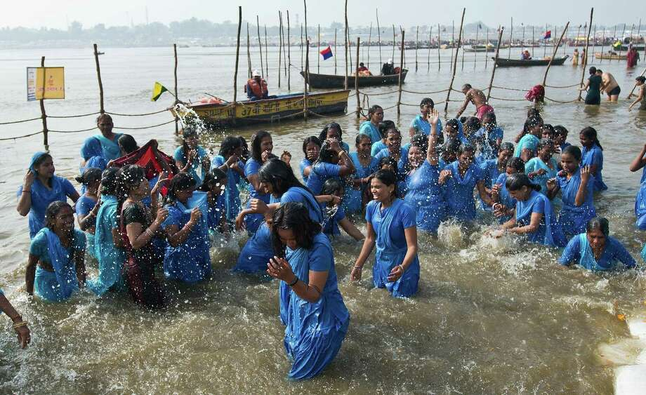 Former manual scavengers take a 'holy dip' at Sangam, the confluence of the Ganges, Yamuna and mythical Saraswati rivers during the Kumbh Mela in Allahabad on February 7, 2013.  100-odd former scavenger women from Rajasthan's Alwar and Tonk districts, rehablitated by NGO Sulabh International, took a holy dip at Sangam, performed puja and had lunch with priests at the Kumbh Mela. Photo: PRAKASH SINGH, AFP/Getty Images / AFP